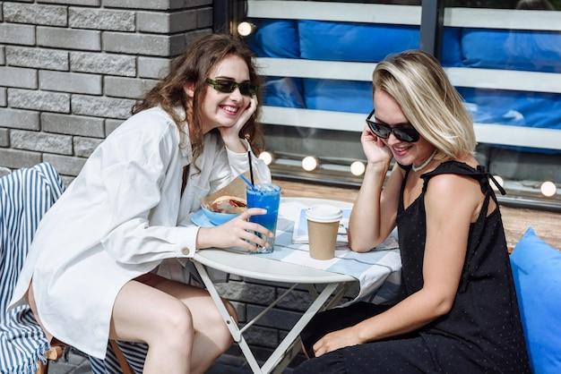 레스토랑의 테이블에 앉아 있는 두 명의 행복한 세련된 여성의 초상화