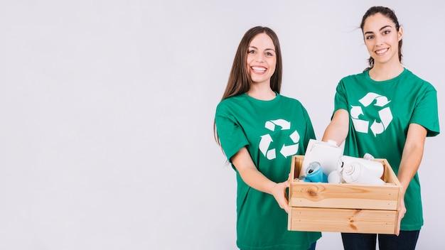 Портрет двух счастливых женщин, держа деревянный ящик, полный бутылок и жестяных банок