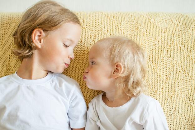 두 명의 즐거운 행복한 자매의 초상 여동생이 누나에게 키스하기 위해 손을 뻗습니다