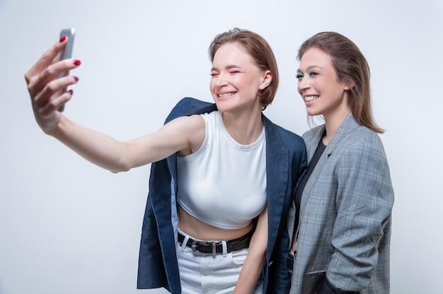 Портрет двух смеющихся женщин в пиджаках, делающих селфи. понятие дружбы. смешанная техника