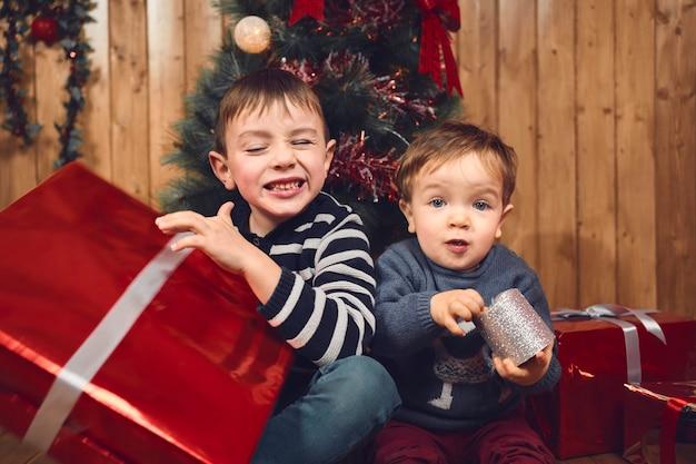 彼らのクリスマスプレゼントでポーズをとってカメラを見ている2人の小さな金髪の男の子の肖像画