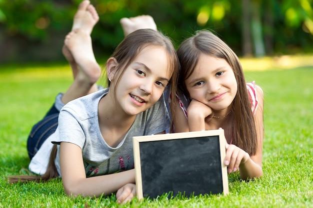 빈 칠판과 잔디에 포즈 두 어린 소녀의 초상화