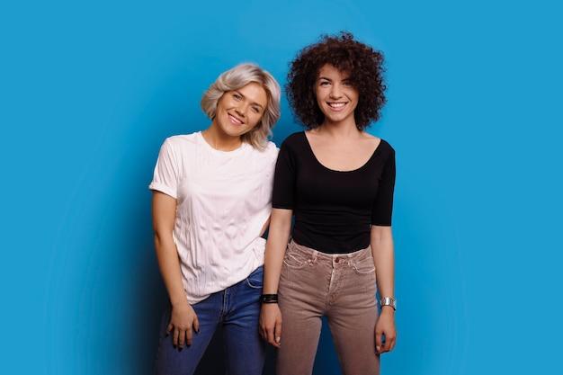 두 사랑스러운 여자 친구의 초상화 하나는 검은 옷을 입고 다른 흰색 파란색 스튜디오 벽에 고립 된 카메라 웃음을보고.