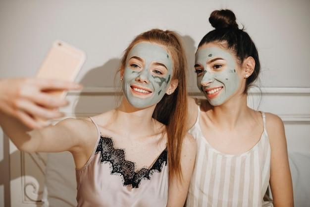 Портрет двух прекрасных молодых женщин, делающих селфи, смеясь, расслабляясь дома с маской для лица на их лице. вечеринка для девочек, отдыхающих дома.
