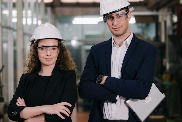 2人の機械工の肖像画は、産業工場のガラスの壁の前に安全ヘルメットを持って自信を持って立っています。