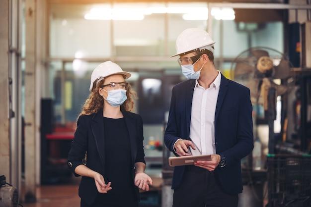 2人の機械工の肖像画は、産業工場のガラスの壁の前にタブレットと安全ヘルメットを持って立っています。