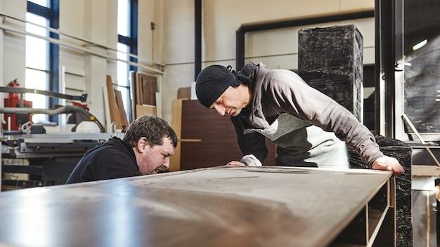 2人の男性労働者の肖像画は、木製の机を見てカメラに戻った