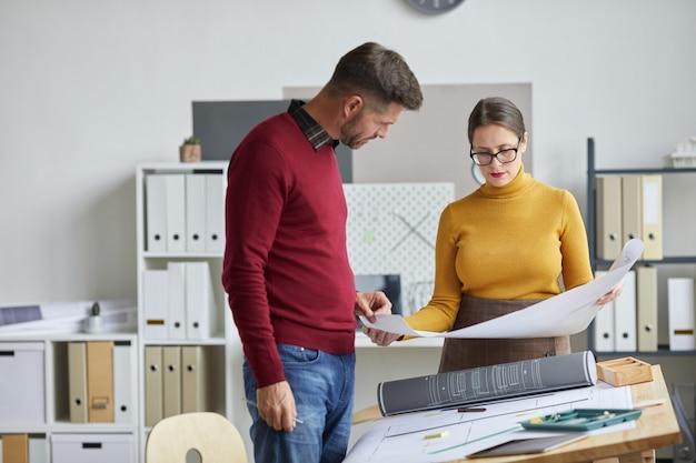 두 성숙한 건축가 남자와 사무실에서 책상을 그리기 서있는 동안 청사진에 함께 작업하는 여자의 초상화,