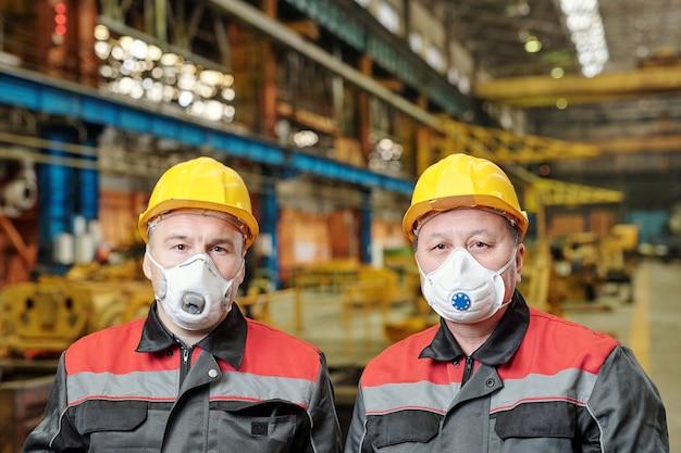 공장에서 일하는 동안 카메라를 보고 있는 보호 마스크를 쓴 두 명의 성숙한 엔지니어의 초상화