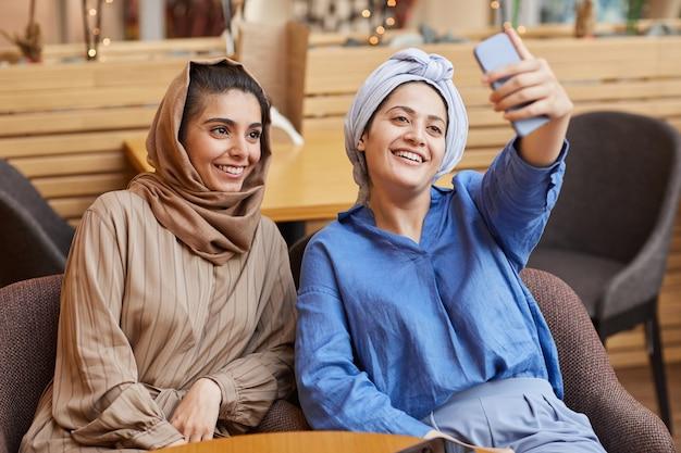 카페에서 휴식을 취하는 동안 스마트 폰을 통해 셀카를 복용하는 두 중동 젊은 여성의 초상화, 복사 공간