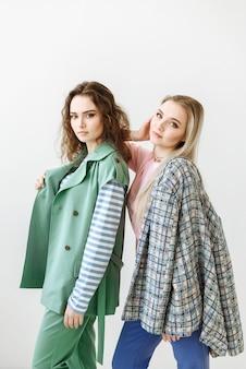 モダンでファッショナブルな服を着てスタジオで白いシーンに一緒に立っている2人のモデルの女性の肖像画
