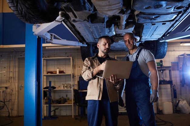 Портрет двух современных автомехаников, стоящих под транспортным средством на автомобильном подъемнике и использующих ноутбук, копировальное пространство