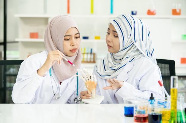Портрет исследователя 2 мусульман проверяя и изучая в лаборатории.