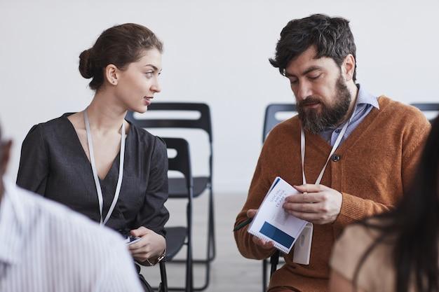 Портрет двух человек в аудитории на бизнес-конференции, мужчина и женщина разговаривают, сидя на стульях в ряд