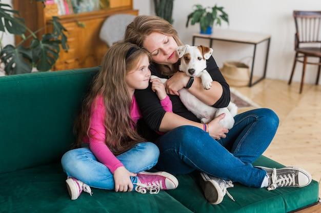 두 사람의 사랑스러운 엄마와 그녀의 아이가 포옹하는 초상화는 함께 편안한 소파에 앉아 자유 시간을 보냅니다