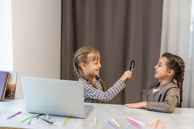 Портрет двух симпатичных привлекательных очаровательных милых милых позитивных забавных веселых жизнерадостных девушек, изучающих предмет, просматривающих предметы, делающих домашнее задание в светло-белом интерьере классной комнаты в помещении
