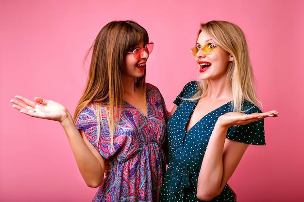 ピンクの壁で楽しい2人の陽気な親友の女性の肖像画。明るい印刷されたヴィンテージの夏のドレスとサングラスを着用し、一緒におしゃべりをして、感情を退出しました。
