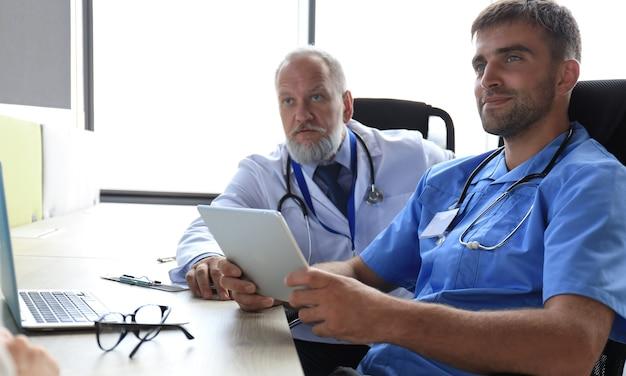병원에서 환자를 상담하는 두 명의 실무자의 초상화.