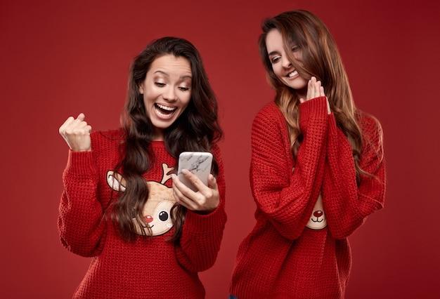 Портрет двух довольно сумасшедших лучших друзей в модном уютном зимнем свитере, кричащих от радости, глядя на телефон
