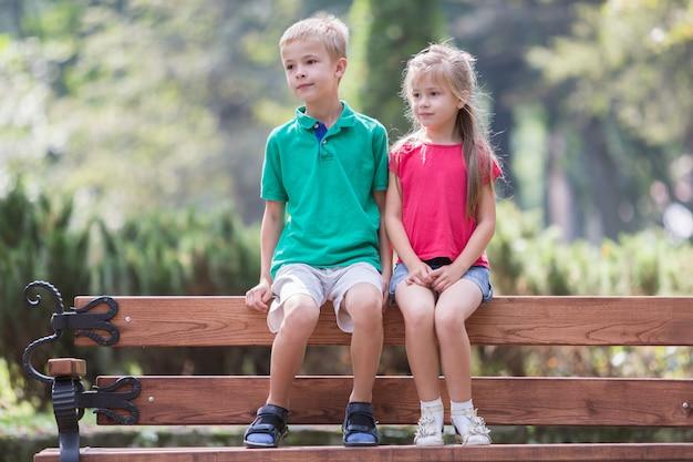 2つのかなりかわいい子供の男の子と女の子の屋外の夏の公園のベンチで楽しい時間の肖像画。