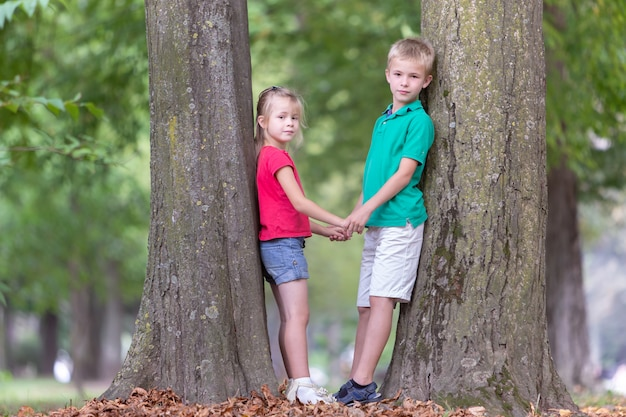2つのかなりかわいい子供男の子と夏の公園屋外で大きな木の幹の近くに立っている女の子の肖像画。