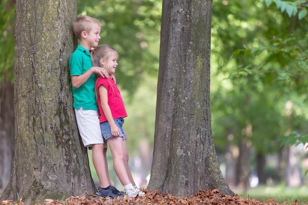 2つのかなりかわいい子供男の子と屋外の夏の公園で大きな木の幹の近くに立っている女の子の肖像画。