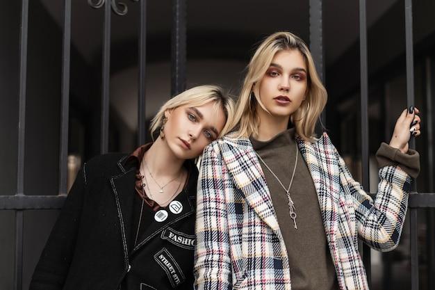 Портрет двух довольно симпатичных подростков с красивыми губами и светлыми волосами в модных куртках на открытом воздухе возле старинных железных ворот