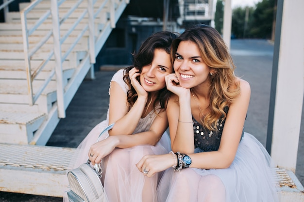 屋外の階段に座っているチュールスカートの2人のかわいい女の子の肖像画。彼らは笑っている。