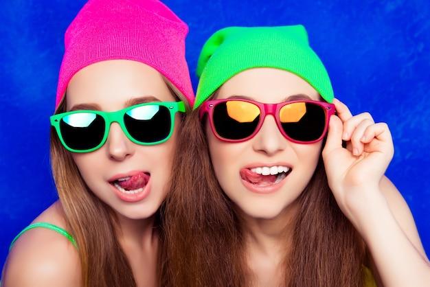 舌を示す帽子と眼鏡の2人のかわいい姉妹の肖像画