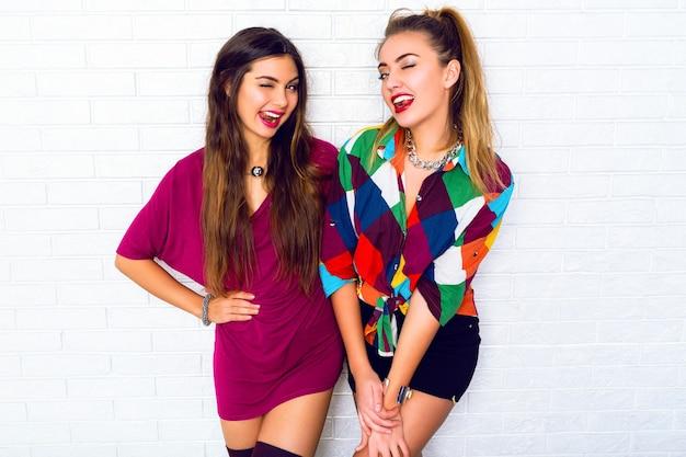 Портрет двух симпатичных подружек-подростков, улыбающихся и позирующих