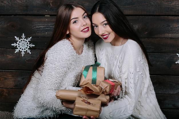 Портрет двух хорошеньких молодых женщин с рождественскими подарками