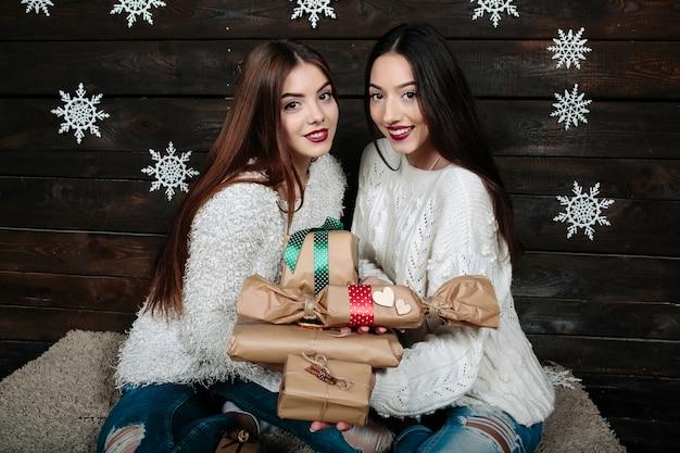 クリスマスプレゼントを持つ2つのかなり若い女性の肖像画
