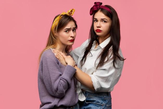 Портрет двух грустных привлекательных стильных подруг в стильной одежде и аксессуарах, позирующих изолированно и обнимающих друг друга