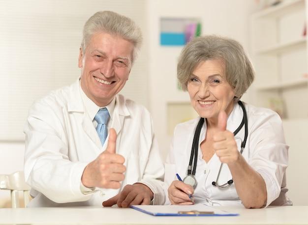 두 수석 의사의 초상화는 엄지손가락을 보여줍니다