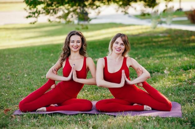 Портрет двух безмятежных молодых красивых женщин на сеансе медитации на открытом воздухе