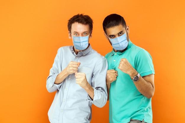 ボクシングの拳で立って、ウイルスや問題に対して攻撃または防御する準備ができているサージカルマスクを持つ2人の深刻な若い労働者の男性の肖像画。オレンジ色の背景に分離された屋内スタジオショット