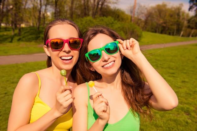 Портрет двух сексуальных женщин в очках, держащих леденцы на палочке