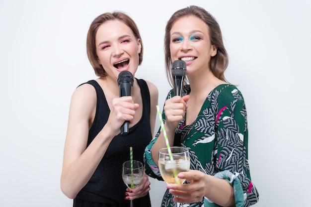 Портрет двух поющих девушек с очками в руках. концепция караоке. смешанная техника