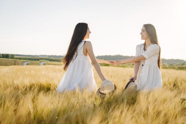 필드에 긴 머리를 가진 흰색 드레스에 두 자매의 초상화
