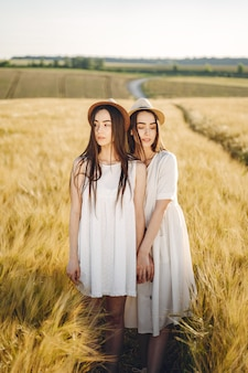 Портрет двух сестер в белых платьях с длинными волосами в поле