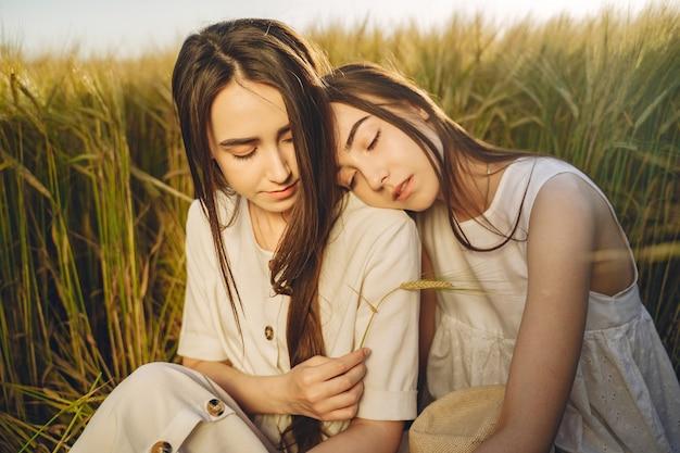 フィールドで長い髪の白いドレスを着た2人の姉妹の肖像