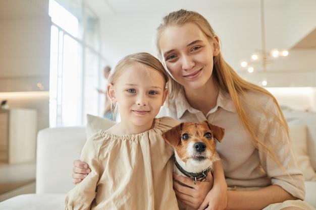 Портрет двух сестер, позирующих с собакой, сидя на диване в домашнем интерьере
