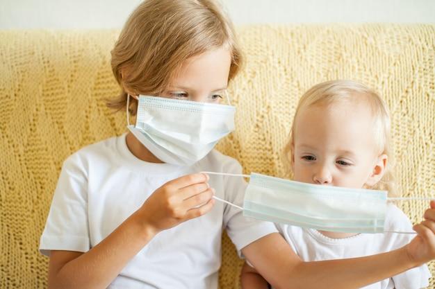 의료 보호 마스크를 쓰고 있는 두 자매의 초상화 누나는 동생을 돕습니다