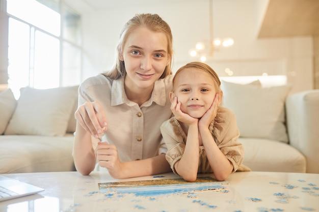 Портрет двух сестер, решающих головоломку вместе, наслаждаясь временем в помещении дома
