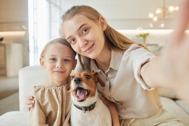 Портрет двух сестер, делающих селфи с собакой, сидя на диване в домашнем интерьере