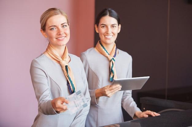 Портрет двух улыбающихся бортпроводников, передающих билеты пассажиру, стоя на стойке регистрации в аэропорту,