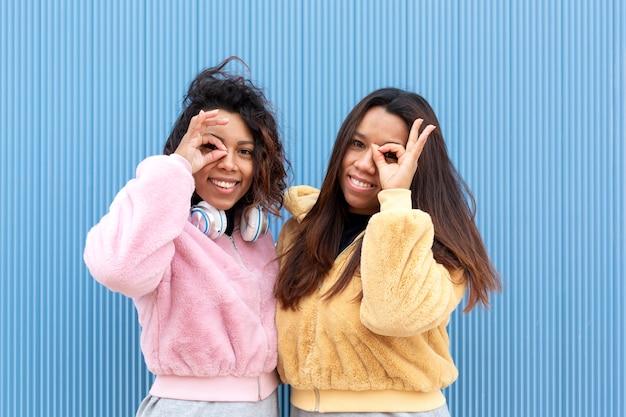 좋아의 상징을 형성하는 그들의 얼굴 가까이에 그들의 손가락을 넣어 두 웃는 친구의 초상화. 그들은 파란색 배경에 있습니다. 텍스트를위한 공간.