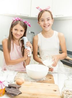 파이 요리와 반죽을 만드는 두 웃는 여자의 초상화