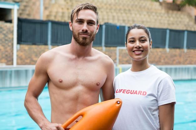 Портрет двух улыбающихся спасателей, стоящих у бассейна