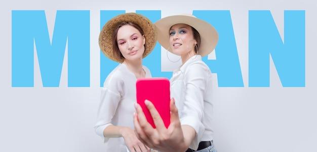 Портрет двух улыбающихся женщин, делающих селфи на фоне рекламного щита с надписью «милан». концепция путешествия. смешанная техника